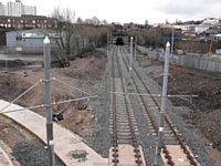 Metrolink construction at Werneth, 4 March 2012:      viewed from  Featherstall Road  the newly laid track heads into the Werneth Tunnel towards Mumps.  On the left the concrete track bed for a later tram route has been laid.