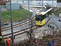 On the first day, rail workers look on as tram 3022 slowly rounds the new curve back onto the original route to Manchester and beyond 27/01/2014. Photo R Clarke