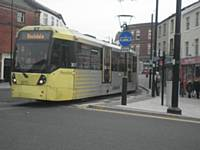 An inbound tram crosses Drake Street in Rochdale on the first day of service into the Town Centre.  J Dillon