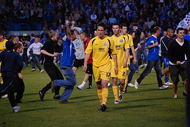 Dismayed Dale players leave the pitch as Gillingham fans begin their celebrations.