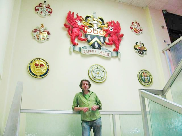 Charlie Oldham with the Oldham Coats of Arms displayed outside the Council Chamber