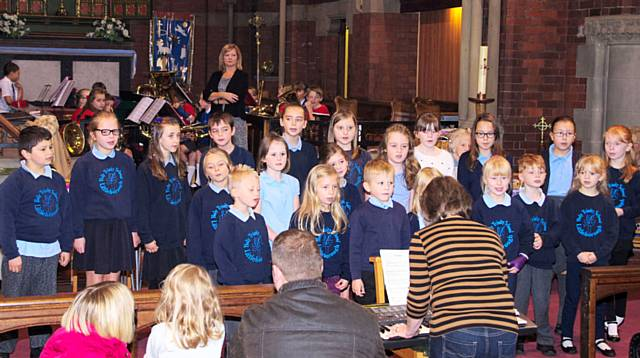 The choir from Holy Trinity, Littleborough with a junior brass band in the background, comprising young musicians from St Andrew's Primary School and from Junior Blast
