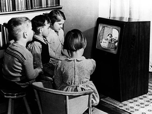 Children gathered around a black and white TV set watching Andy Pandy on the BBC in the 1950s