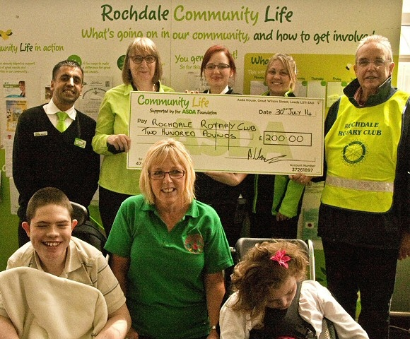Staff from Asda present a cheque to Rotarian David Acton and staff and students from Redwood School