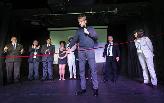 Hopwood Depree cutting the ribbon at the opening of the new Hopwood Theatre in front of College staff, students and invited guests