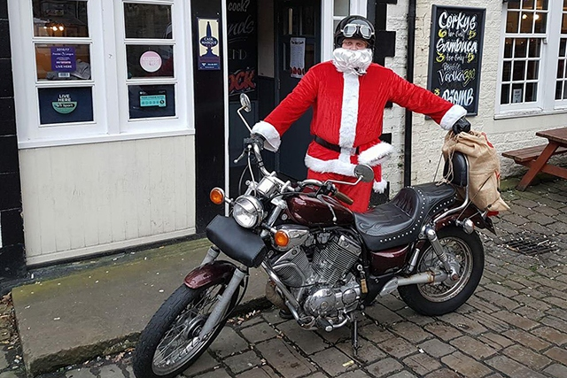 Santa with his motorcycle ready to deliver a sack of toys to the women's refuge