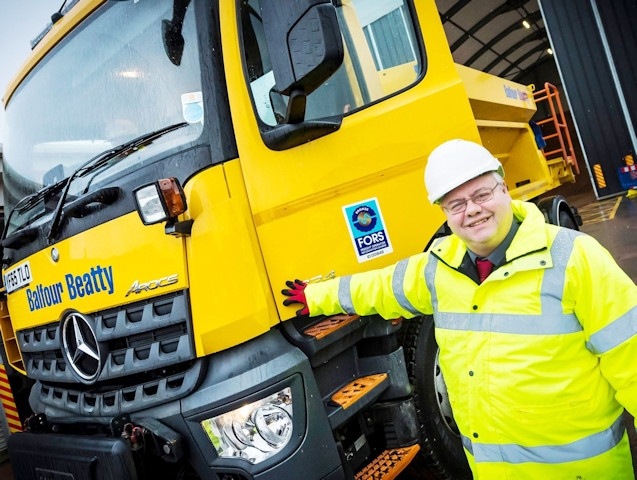 Councillor Neil Emmott with one of the gritters at the council's Princess Street depot in Rochdale