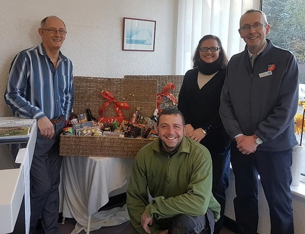 NEEVA Chairman Paul Ellison and Co-op manager Carl England with the Christmas hampers and NEEVA members, Amor and Andrew