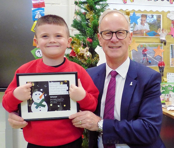 Rochdale Borough Council chief executive Steve Rumbelow meets Ellis Kelly at Springside Primary School in Rochdale, presenting him with a framed version of his design