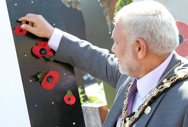 Mayor Mohammed Zaman places a poppy on the Memorial Pop-up Garden