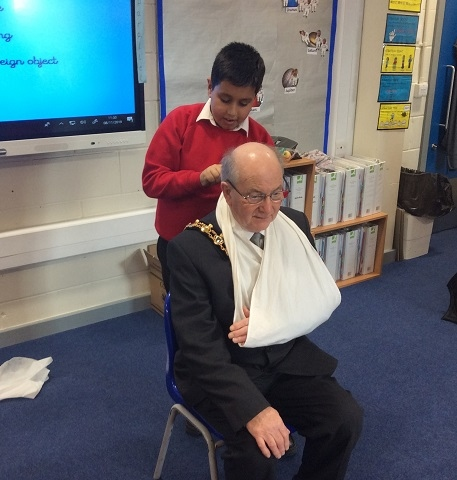 Children at Hamer Community Primary School demonstrate the first aid skills on Mayor Billy Sheerin