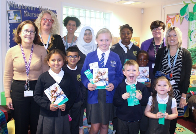Pupils at Broadfield Primary School celebrate the launch of the library card for every child scheme, with children's champion Erin Buckley, teachers and Councillor Janet Emsley, cabinet member for libraries