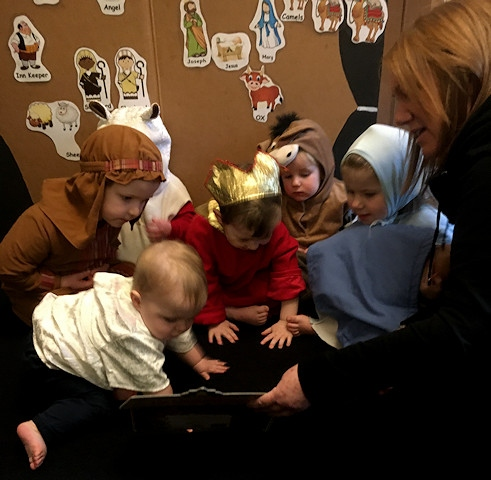 Céline Coldman with some of the children she looks after, reading the Nativity Story
