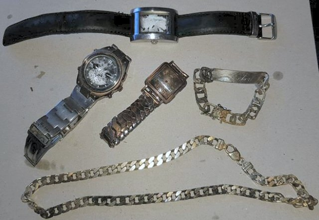 The items recovered from the canal, including the necklace engraved with 'Robert'