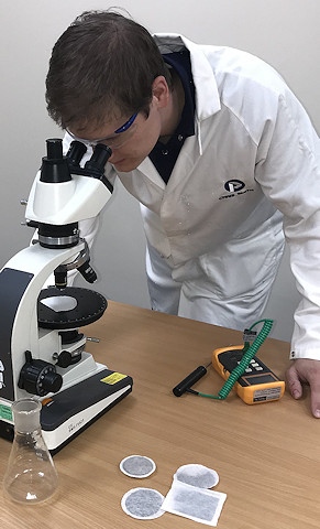 A man looks at the new compostable paper under a microscope