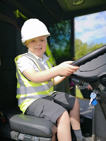 Healey Primary pupil George Cornall at the wheel of the bin lorry