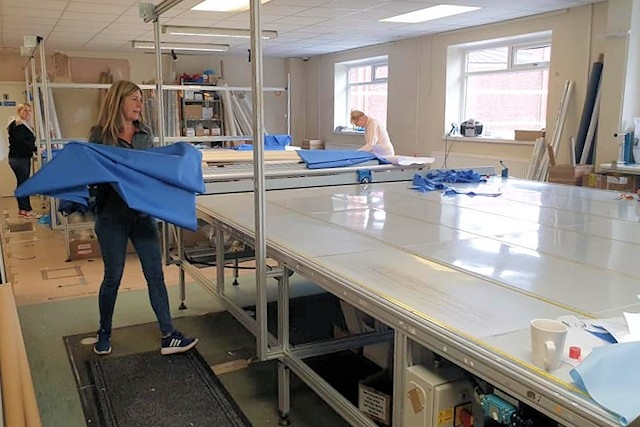 Staff at Mike Goldrick Blinds cutting out fabric to be made into scrubs