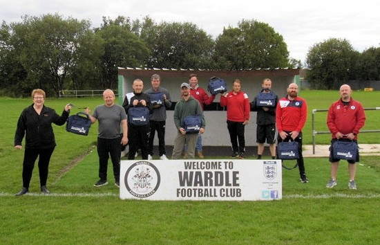 Bev Wrigley from Engaging Safety (far left) presents the first aid kits to Wardle JFC