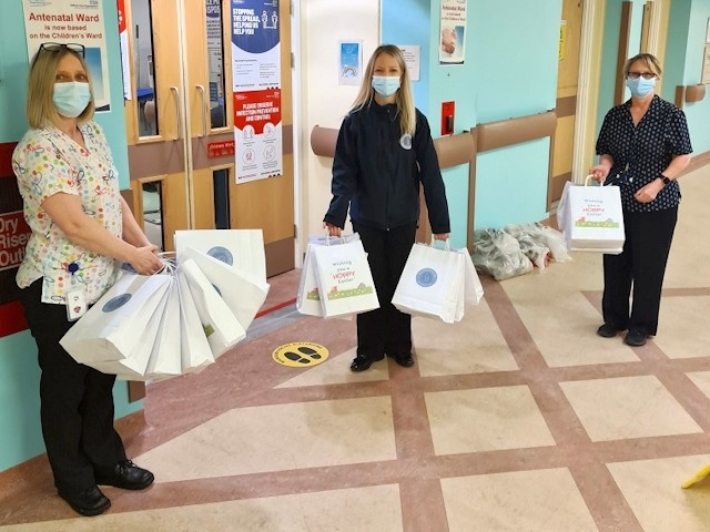 Middleton Shopping Centre staff Nicky Barrett and Ilyas Aslam donate items to Lisa McMahon from the children's ward