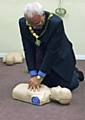 Deputy Mayor Ray Dutton practising CPR at Milnrow Village Practice