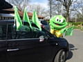 Springy the Hospice Frog decorating cars with Go Green flags