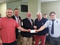 Rochdale RUFC club captain Tom Callaghan, Chairman Iain Coates and President Steve Helliwell present a cheque for �1000 to the Carlisle captain and president