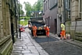 Workmen put temporary tarmac where the setts have been removed on King Street