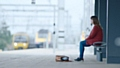 A person sitting alone and isolated on a station platform - Small Talk Saves Lives, says Samaritans
