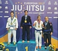 Sophie Cox on the podium after winning gold, European Masters blue belt lightweight