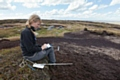 A scientist from Moors for the Future Partnership records the height of the water table on an area of bare peat moorland