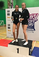 Izzy Bradley-Harris and Hannah Langan with medals and trophies for their success in the club competition at Bury