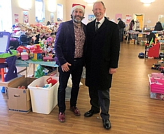 Martyn Allen and Frank Coates surrounded by hundreds of Christmas gifts, donated for struggling parents at Kavanagh & Coates Funeral Services in Heywood