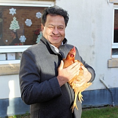 Councillor Iftikhar Ahmed, cabinet member for adult care, with one of the hens at Cleggsworth House Care Home