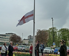 The Saint George cross being raised