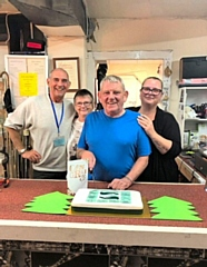 Michael Bamford (centre), who runs Re-Use Littleborough, cut the 1st birthday cake with volunteers