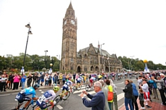 The peloton passes along the Esplanade in front of the town hall