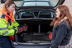 Highways England traffic officer Kelly Rudge checks engine oil with student Shelby Thomas