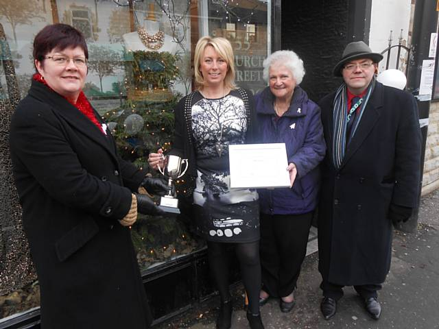 Joanne Matthews from Best Dressed accepting the LEAF Christmas Window Trophy from Councillors Janet Emsley, John Hartley and Ann Stott.
